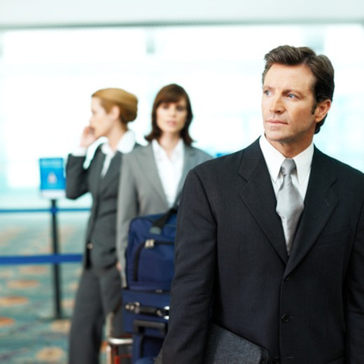 close up of businessman and two businesswomen one who is talking on mobile phone the other standing beside luggage trolley queuing at airport : Stock Photo