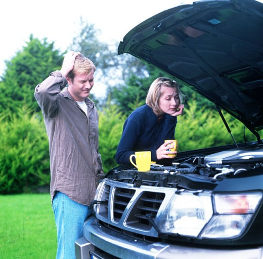 Stock Photo: 1491R-100044 view of a couple looking into the bonnet of their broken down car