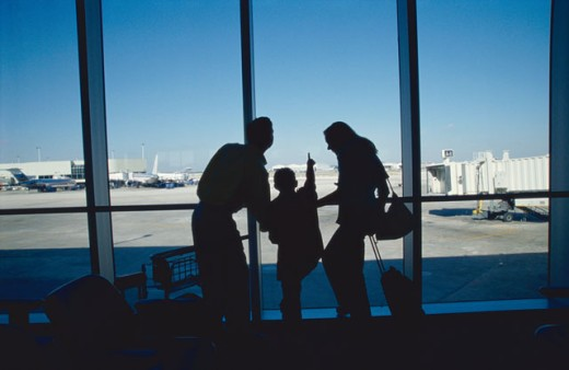 family watching an airport runway from a window (silhouette) : Stock Photo