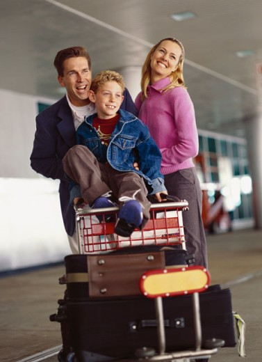 front view of a couple pushing a luggage trolley with their son (8-10) sitting on it : Stock Photo
