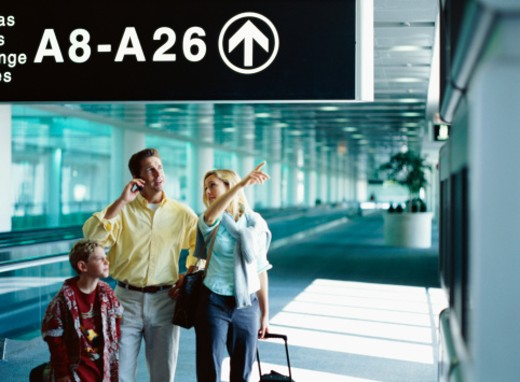 Stock Photo: 1491R-101194 view of parents and a son (8-10) at an airport under a gate number sign