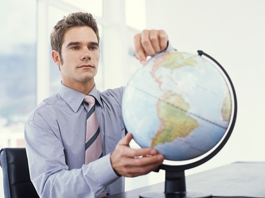 Businessman pointing at west coast of the USA on globe : Stock Photo