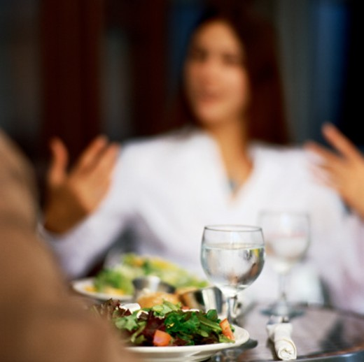 Stock Photo: 1491R-101231 young woman sitting and talking at the dinner table
