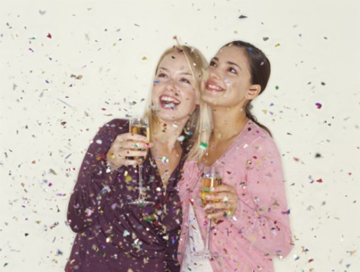 Two young women holding champagne and being showered in confetti : Stock Photo
