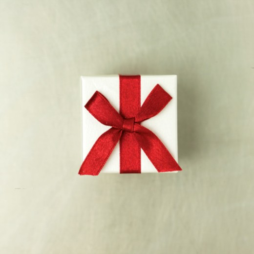 Gift wrapped with red ribbon, close-up, overhead view : Stock Photo