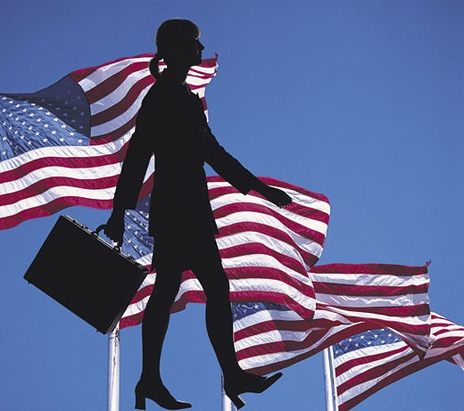 Female with briefcase against American flags : Stock Photo