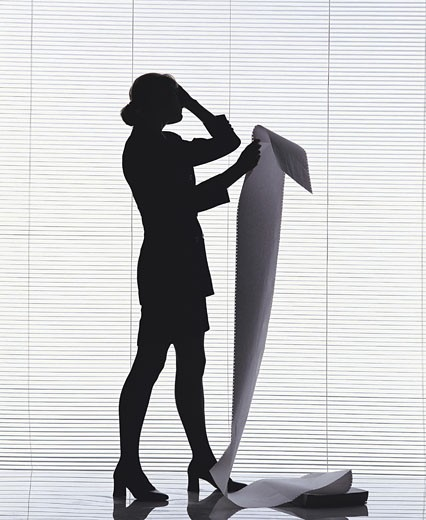 Female reading computer printout : Stock Photo