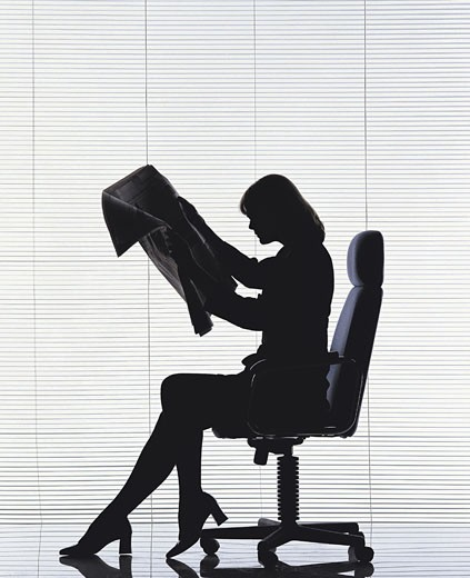 Female sitting on office chair reading newspaper : Stock Photo