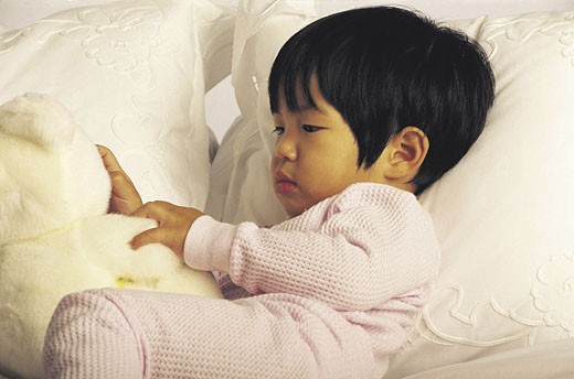 Asian American baby on bed : Stock Photo