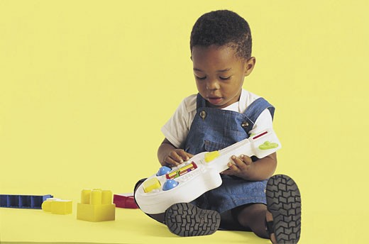 Black American boy playing with toy guitar : Stock Photo