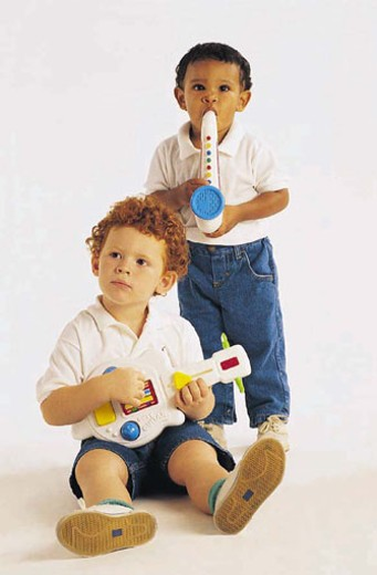 Stock Photo: 1491R-1015098 Asian American boy and white boy playing with toy musical instruments