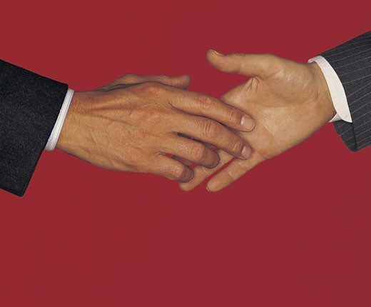 Stock Photo: 1491R-1015370 Business men about to shake hands, red background