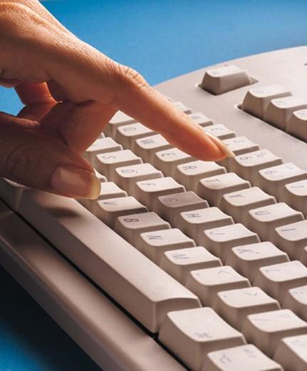 Businesswoman, finger touching key on computer keyboard : Stock Photo