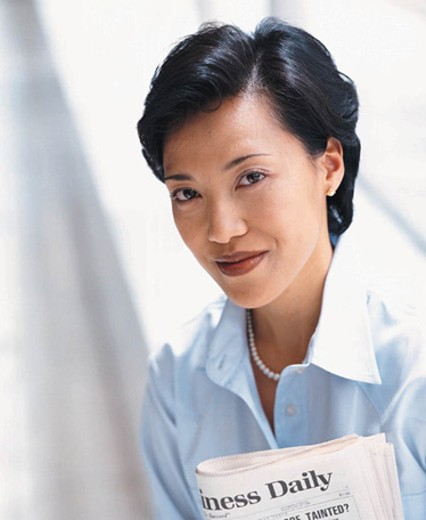 Woman holding newspaper, smiling : Stock Photo