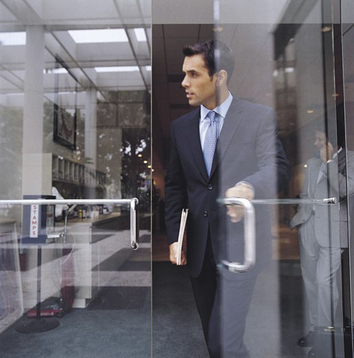 Man leaving office building; second man in background talking on cellular phone : Stock Photo