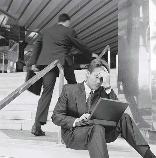 Stock Photo: 1491R-1015675 Man sitting on steps of building, laptop computer on lap, leaning forehead against hand in dismay