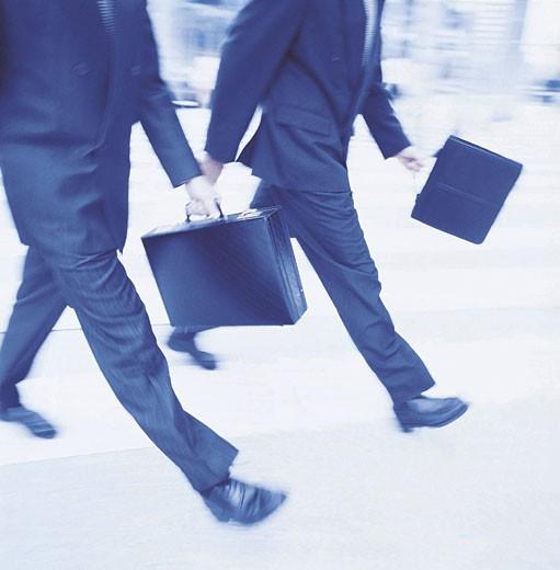 Two men walking across crosswalk : Stock Photo