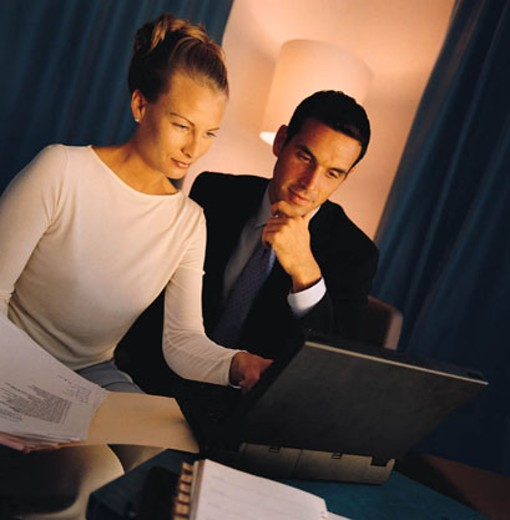 Woman and man looking at laptop computer screen together; woman holding open folder : Stock Photo