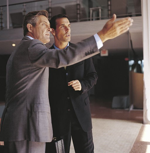 Older man standing next to younger man, gesturing with arm : Stock Photo