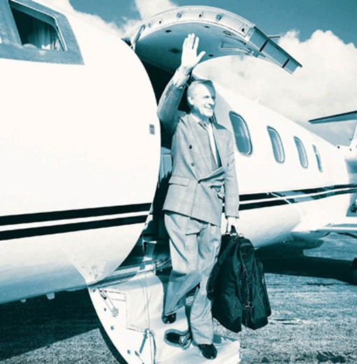 Man stepping out of company jet, waving and smiling : Stock Photo