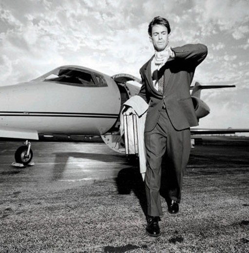 Man striding away from company jet on tarmac, looking at wristwatch : Stock Photo