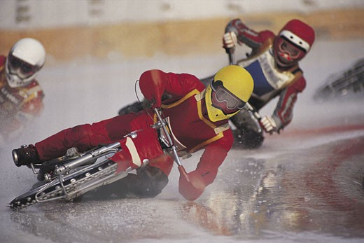 Motorcycle racers leaning into turn : Stock Photo