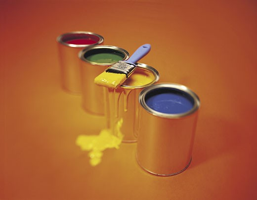 Stock Photo: 1491R-1018148 Red, green, yellow and blue paint in cans, with brush