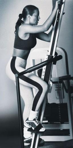 Woman using climbing machine : Stock Photo