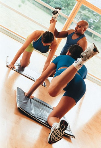 Two women performing donkey kick exercise as trainer watches : Stock Photo