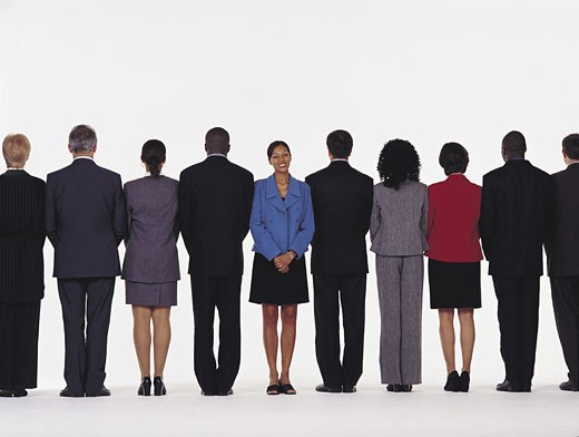 Line of business men and women, one woman facing opposite direction : Stock Photo