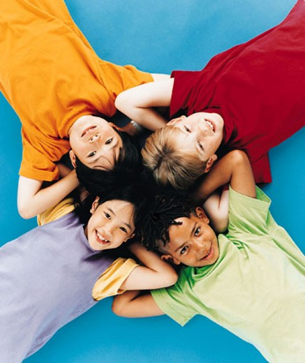 Four children lying on backs on ground in cross formation : Stock Photo