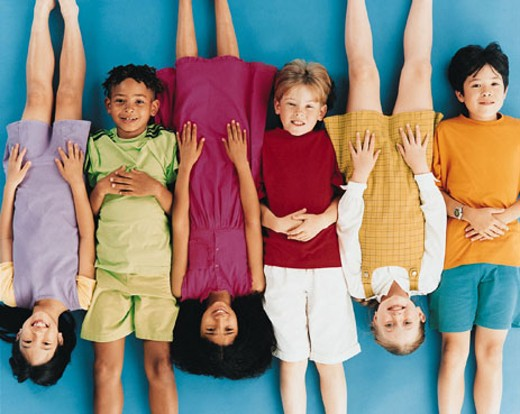 Children lying on ground, alternating head to feet : Stock Photo