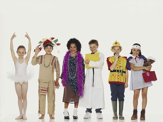 Children wearing costumes, standing in row : Stock Photo