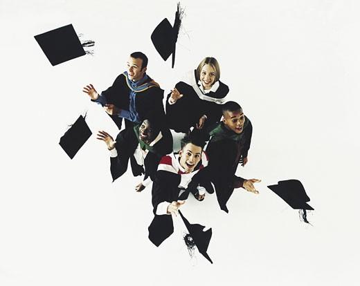 Teenage graduates throwing caps into air : Stock Photo