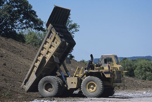 Heavy construction, road building, large dump truck emptying load : Stock Photo
