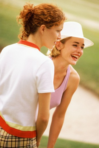 Two women standing on golf course, one laughing : Stock Photo