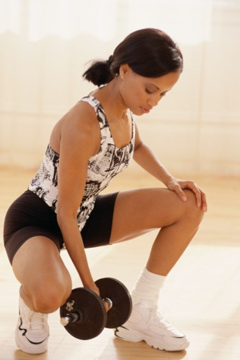 Woman squatting, lifting dumbbell : Stock Photo