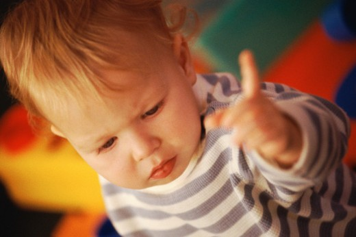 Baby in striped shirt, pointing finger : Stock Photo