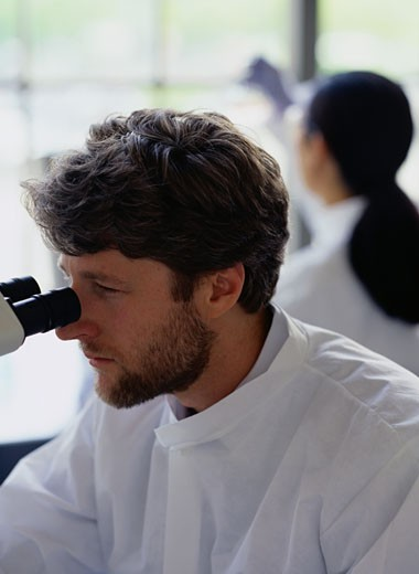 Chemist Using a Microscope in a Laboratory : Stock Photo