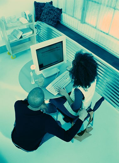 Stock Photo: 1491R-1029531 Couple Using a Computer at an Internet Caf?