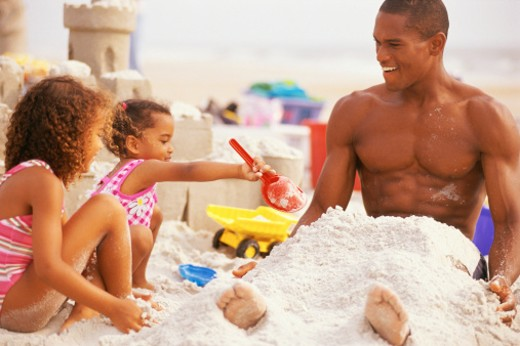 Girls covering father with sand at beach : Stock Photo