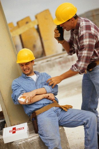 Man holding injured arm, other man on walkie talkie : Stock Photo