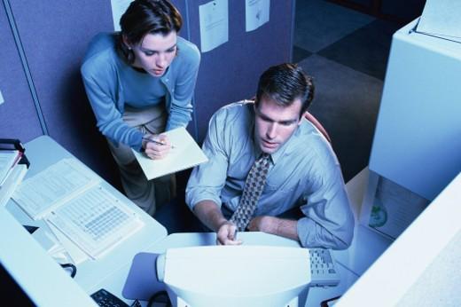 Man and woman looking at computer terminal : Stock Photo
