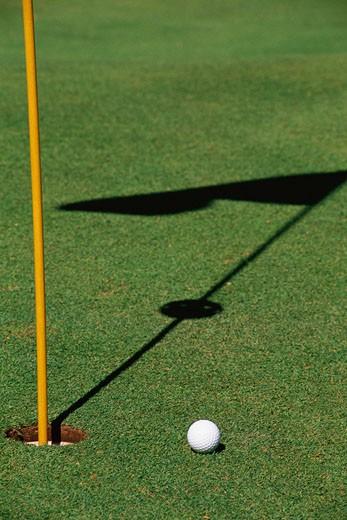Golf ball near hole : Stock Photo