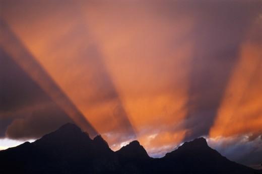 Sunlight filtering over mountain ridge : Stock Photo
