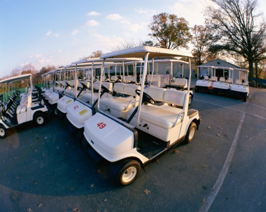 Rows of golf carts in parking lot : Stock Photo
