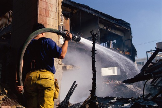 Firefighter aiming hose at charred building : Stock Photo