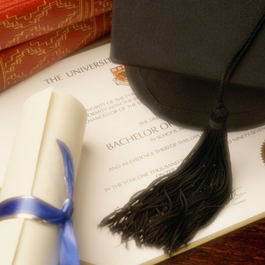 Scroll, textbooks and mortarboard cap resting on college diploma : Stock Photo
