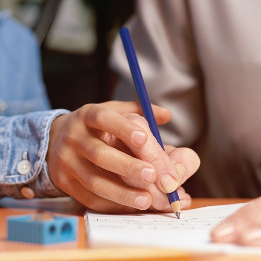 Child's hand guiding adult's hand through writing exercise : Stock Photo