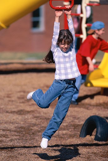 Girl playing on playground, hanging from jungle gym : Stock Photo